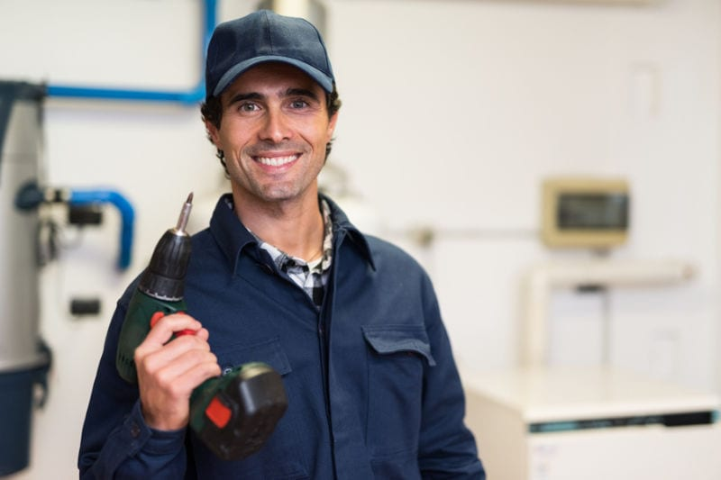Smiling worker holding a screwdriver